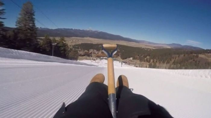 Waghalsiges Rennen: Mit der Schneeschippe den Berg hinunter