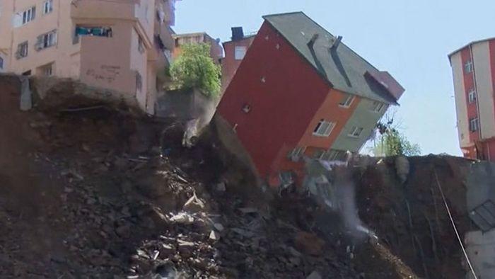 Vierstöckiges Wohnhaus stürzt Abhang hinunter